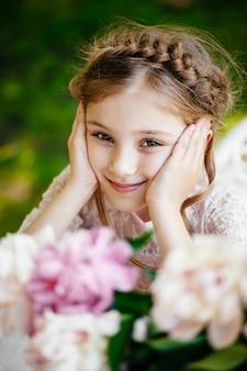 Portrait of a beautiful little girl in flowers