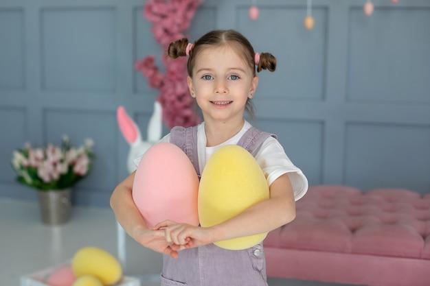 Портрет красивая маленькая девочка играет с пасхальными яйцами девушка держит страусиные яйца маленький фермер