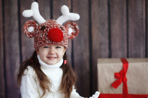 Portrait of a beautiful little girl in the red sweater. portrait of a cute little girl among the christmas decorations. girl rides a reindeer-rocking a hat with horns.