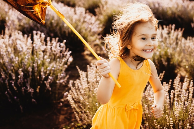 Portrait of a beautiful little girl running holding a gold balloons laughing in a field of flowers .