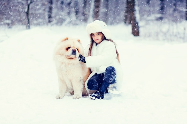 Portrait of the beautiful little girl with a dog in the winter wood