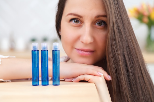 Portrait beautiful long hair young girl holding skincare cosmetics, tubes with face cream, body mask, serum, lip balm.