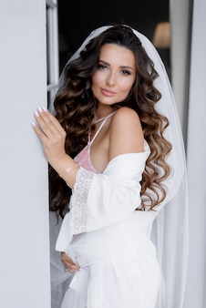 Portrait of beautiful longhaired brunette bride with curls dressed in white silk robe