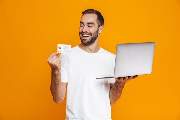 Portrait of beautiful man 30s in white t-shirt holding silver laptop and credit card, isolated