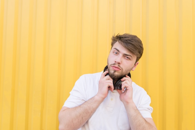 Portrait of a beautiful man with headphones on the neck against a yellow wall