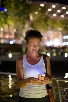 Portrait of beautiful mature tourist woman enjoying life while travelling in singapore city