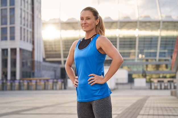Portrait of beautiful middle aged woman in sportswear smiling away standing outdoors ready for