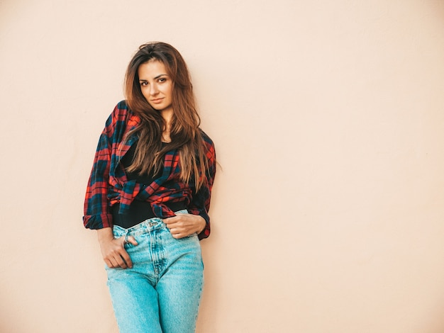 Portrait of beautiful model. female dressed in summer hipster checkered shirt and jeans. trendy girl posing near wall in the street