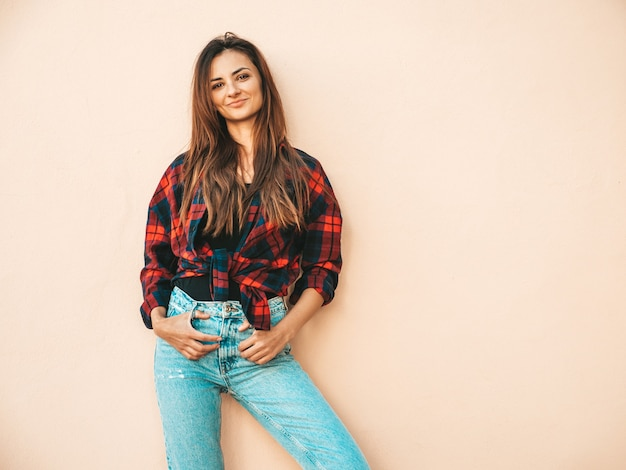 Portrait of beautiful model. sexy female dressed in summer hipster checkered shirt and jeans. trendy girl posing near wall in the street