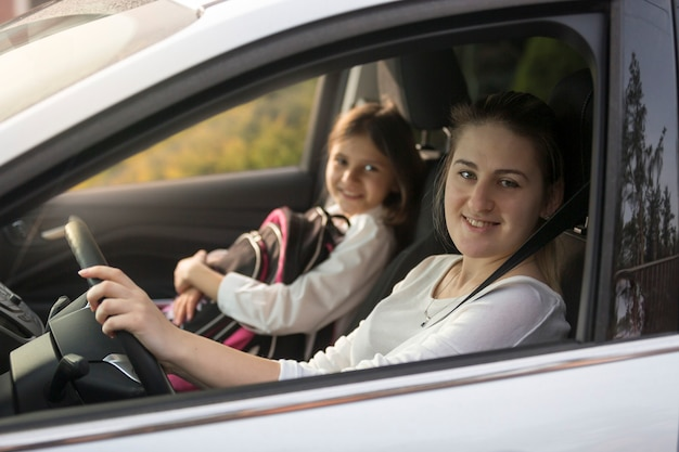 Portrait of beautiful mother driving car with daughter to school