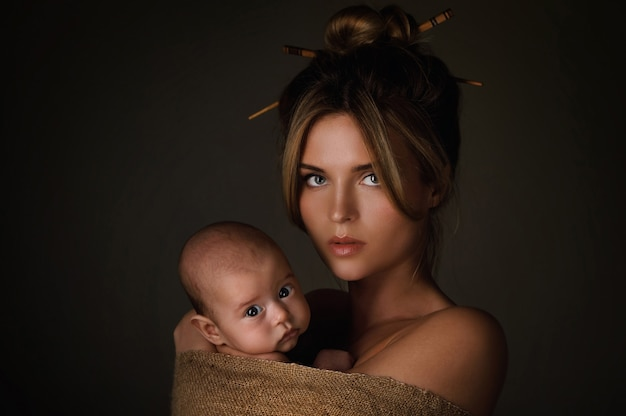 Portrait of beautiful mother and her little baby are wrapped in sackcloth