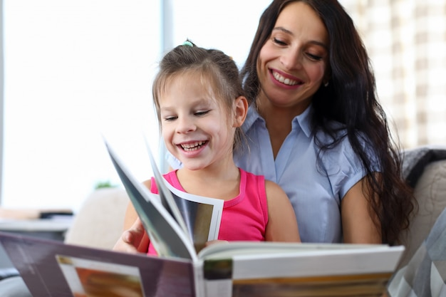 Portrait of beautiful mother teaching declaiming happy daughter. lovely woman and little girl looking at magazine with happiness. childhood and motherhood concept