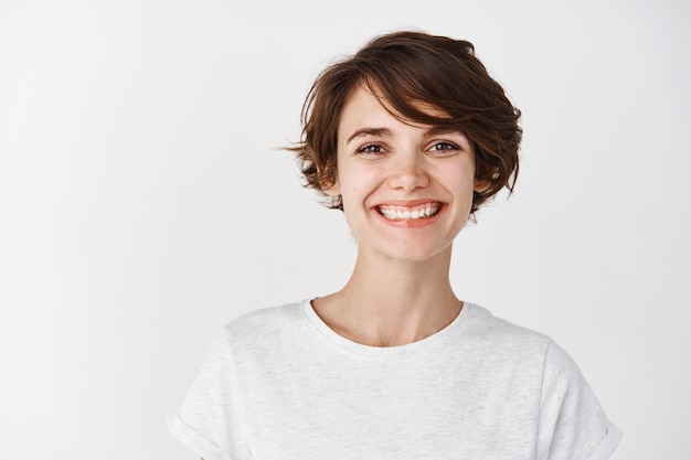 Portrait of beautiful natural girl without makeup, smiling happy , standing in t-shirt against white wall