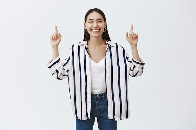Portrait of beautiful natural and stylish woman in jeans and striped blouse, lifting hands and pointing up with index fingers, smiling joyfully, being amused and entertained over gray wall