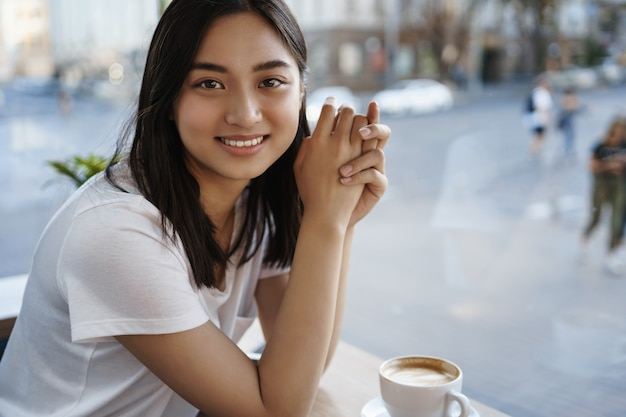 Portrait of beautiful natural woman drinking coffee in cafe alone, sitting near window, smiling at camera happy.