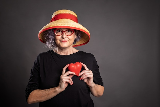 Portrait of beautiful older woman holding a red heart