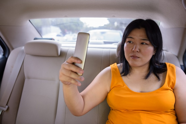Portrait of beautiful overweight asian woman inside the car around the city of bangkok, thailand