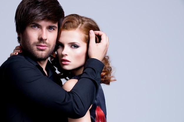 Ritratto di bella coppia appassionata innamorata abbracciata su sfondo grigio