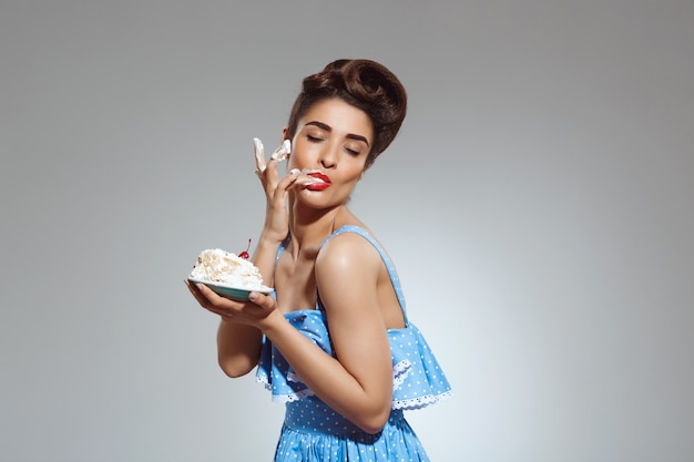 Portrait of beautiful pin-up woman eating cake