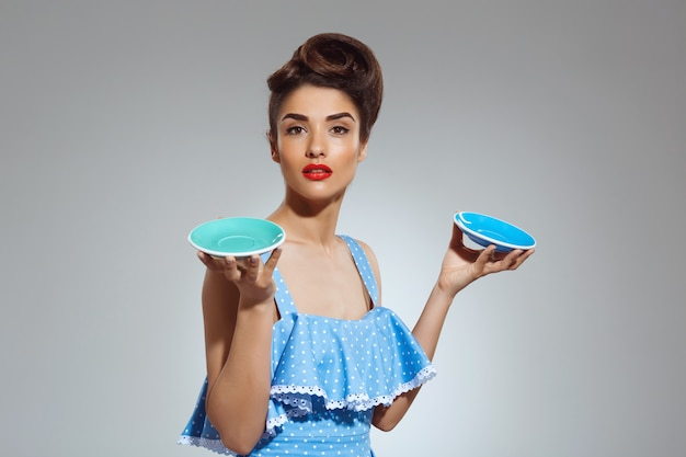 Portrait of beautiful pin-up woman holdig two plates
