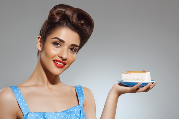 Portrait of beautiful pin-up woman holding cake in hands