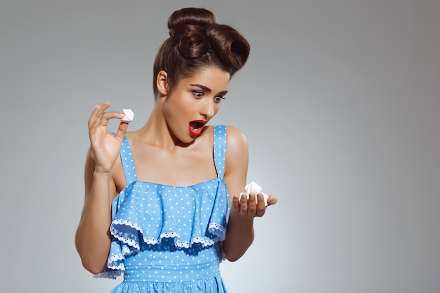 Portrait of beautiful pin-up woman holding sweeties in hands