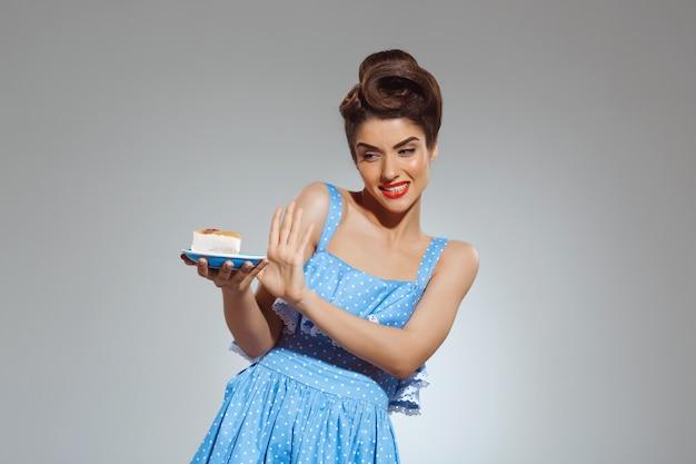 Portrait of beautiful pin-up woman refusing eating cake