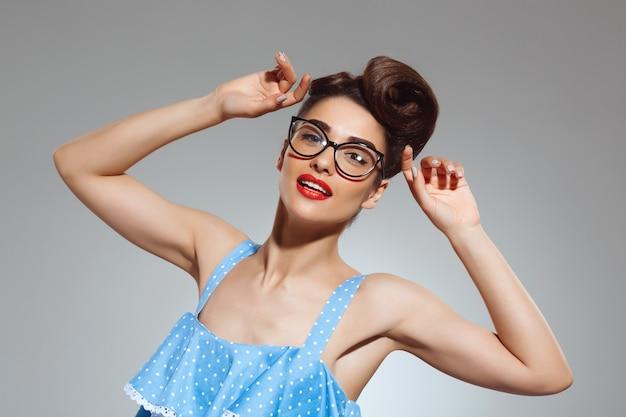 Portrait of beautiful pin-up woman wearing glasses