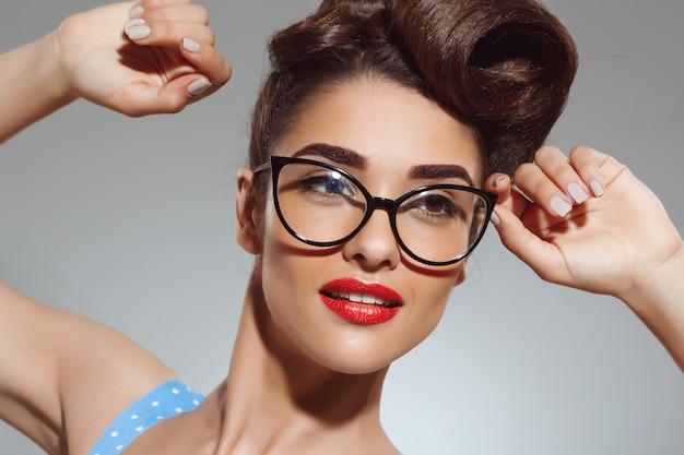 Ritratto di bella donna pin-up con gli occhiali