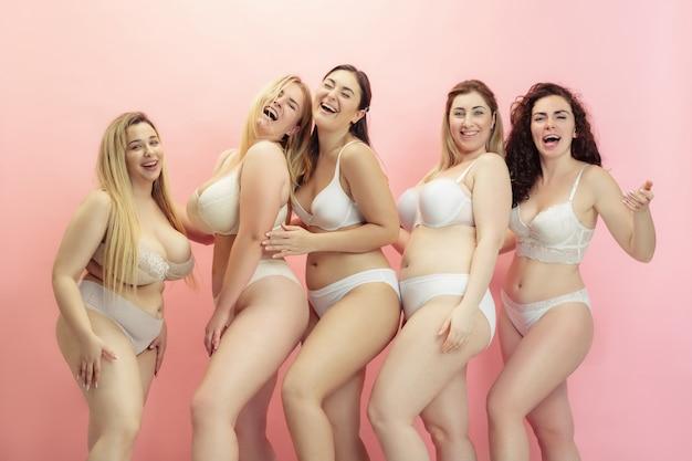 Ritratto di belle giovani donne plus size in posa sul rosa