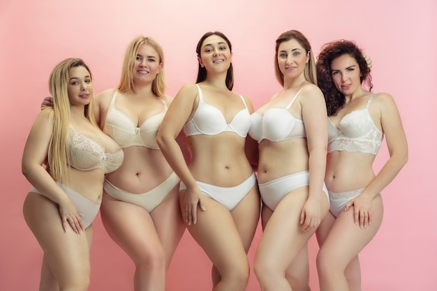 Portrait of beautiful plus size young women posing on pink