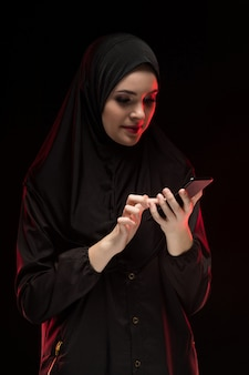 Portrait of beautiful positive friendly young muslim woman wearing black hijab holding mobile phone