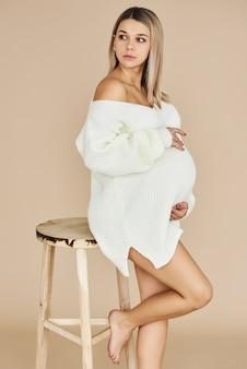 A portrait of beautiful pregnant girl dressed in white sweater in a beige background.