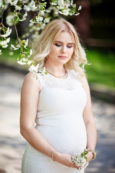 Portrait of beautiful pregnant woman in the flowering park. young happy pregnant woman enjoying life in nature.