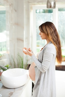 Portrait of a beautiful pregnant woman in home clothes who applies cream to her face in front of a mirror in the bathroom. morning routine. self-care. waiting for the baby. high quality photo