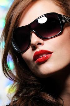 Ritratto di bello fronte femminile grazioso con occhiali da sole moda glamour su di esso