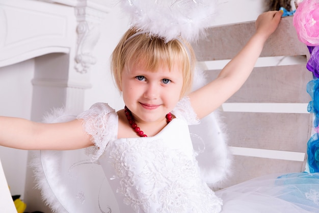 Portrait of beautiful princess girl in white dress with white nimbus and wings