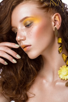 Portrait of beautiful red-haired girl with brightly colored art makeup and curls. beauty face.