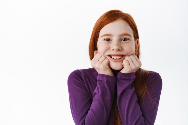 Portrait of beautiful redhead child, little ginger girl with freckles touch cheeks and smiling happy at front, look adorable and cute, white wall
