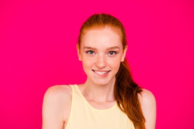 ピンクの壁に隔離の肖像画の美しい赤毛の女の子