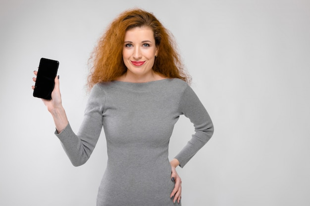 Portrait of beautiful redhead happy smiling young woman in gray clothes showing mobile phone