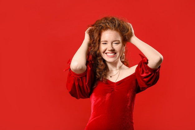 Portrait of beautiful redhead woman on color background