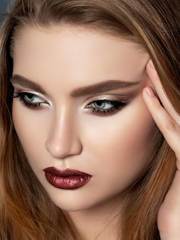 Portrait of beautiful redhead woman with evening makeup touching her face. golden smokey eyes and dark read lips.