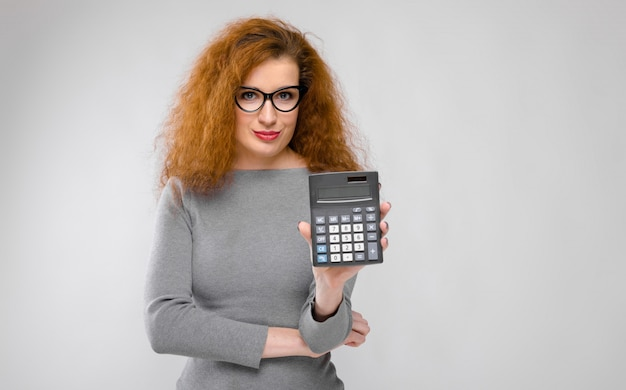 Portrait of beautiful redhead  young woman in gray clothes in glasses showing calculator on gray wall