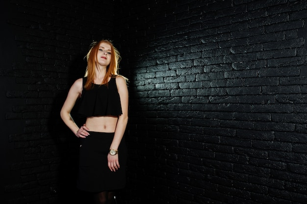 Portrait of a beautiful redheaded girl in black top and black skirt posing in the studio next to the brick wall.