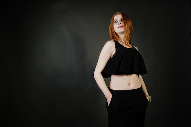 Portrait of a beautiful redheaded girl in black top and black skirt posing in the studio next to the grey wall.