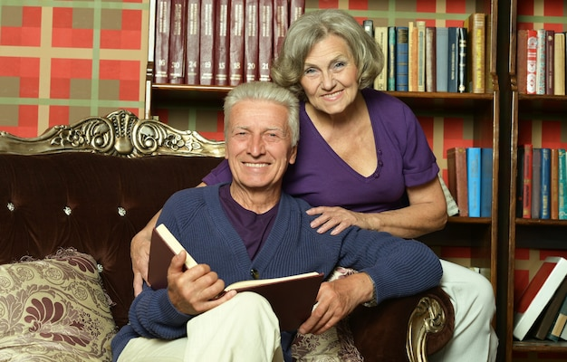Portrait of beautiful retired couple reading book