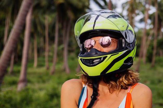 Portrait of beautiful rider woman in yellow green motorcycle helmet and colorful light summer dress in jungle on tropical field under palm trees.