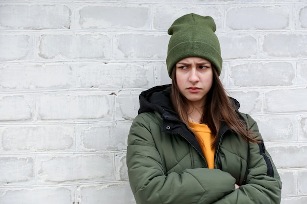 Portrait of a beautiful sad girl in a yellow sweater and khaki hat, which stands near a white brick wall. the concept of emotions and copy space