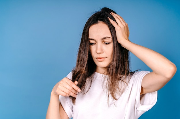 Portrait of a beautiful sad young woman with long hair in her hand. close-up unhappy female model looking at split end hair. hair care concept.